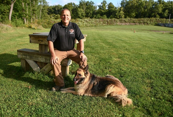 Joe Weyer of the Alliance Police Department started to work on the department's training facility 24 years ago, and has made it world-class destination for police and military training.  Weyer and his dog Sentinel sit at a shooting bench on the 300-meter rifle range at about 125 yards from the target ridge. Photo taken Sept. 18, 2020.  (CantonRep.com / Ray Stewart)