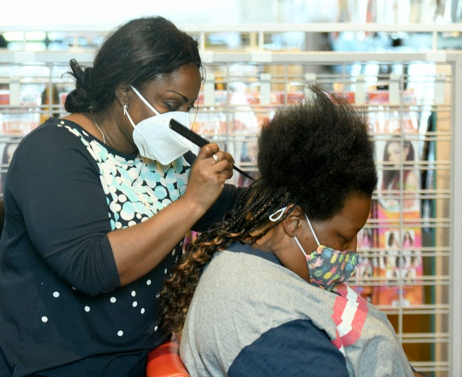Charlotte Engohang works on a clients braid at her new beauty supply store, Akiba's Too Beauty Supply,  in Alliance .  Monday, Sept. 21,  2020. (CantonRep.com / Julie Vennitti)