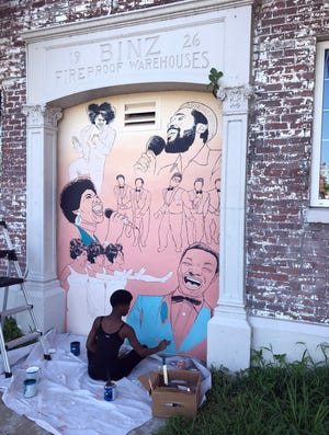 Artist Simoné Corbert works on a mural she has created on a wall of the Westcoast Black Theatre Troupe, depicting (clockwise from upper left), singers James Brown, Marvin Gaye, The Temptations, Nat King Cole, The Supremes and Aretha Franklin.