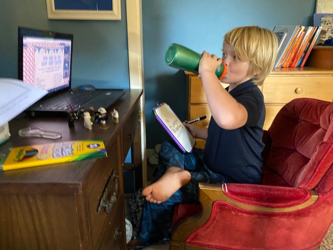 Colin Sellers, age 8, takes a swig of water during his first day of remote learning from home as a third-grader at Southside Elementary School.