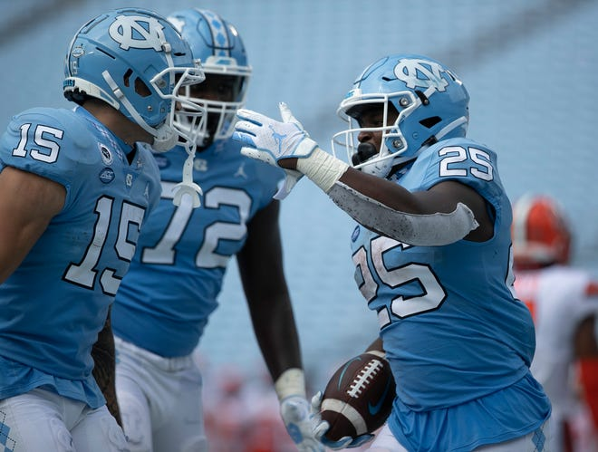North Carolina's Javonte Williams (25) celebrates with teammates after scoring a touchdown to give the Tar Heels' a 24-6 lead in the fourth quarter against Syracuse on Saturday, Sept. 12. The Heels will be able to play the remainder of their home games in front of a limited number of fans.