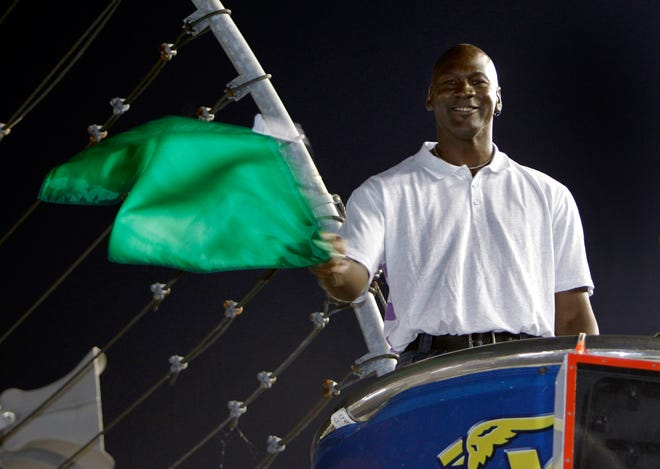 FILE - In this May 22, 2010, file photo, Charlotte Bobcats owner Michael Jordan practices waving the green flag before a NASCAR All-Star auto race at Charlotte Motor Speedway in Concord, N.C. Denny Hamlin is starting his own race car team in partnership Jordan and Bubba Wallace as the driver. (AP Photo/Chuck Burton, File)