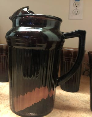 This amethyst-colored glass pitcher, believed to be a Depression-era antique, was likely made after World War II but is of no specific collector interest.