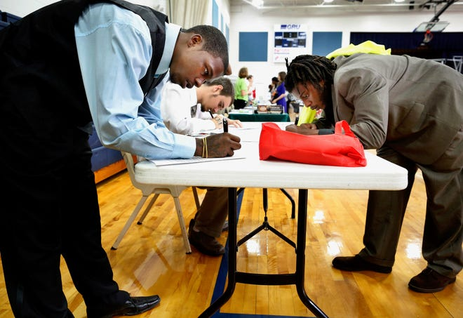 Job seekers fill out applications during a city of Gainesville job fair at the MLK Multipurpose Center in 2015.