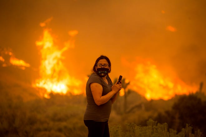 A woman watches as the Bobcat Fire burns in Juniper Hill, Calif., on Sept. 18.