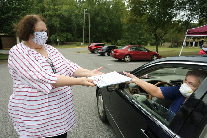 Kathy Byrd presents voter registration documents to Patricia Snow during a drive-thru voter registration drive in the parking lot of the Tuscaloosa Public Library held by the League of Women Voters  Tuesday, Sept. 22, 2020.  [Staff Photo/Gary Cosby Jr.]