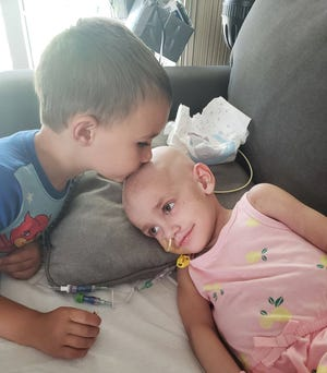 Cole Schreiner, 5, gives his sister, Kinsley, 3, a kiss in this undated photo. After battling cancer for nearly eight months, Kinsley died of cancer on Sept. 13, 2020.