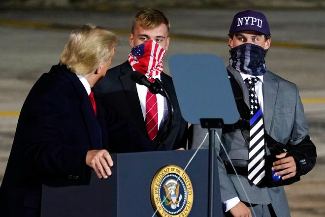 President Donald Trump brings two football players from Little Miami High School who were suspended for a short time for carrying flags that showed support for law enforcement at the start of a game on Sept. 11, onto stage as he speaks during a campaign rally at Eugene F. Kranz Toledo Express Airport, Monday, Sept. 21, 2020, in Swanton, Ohio. (AP Photo/Alex Brandon)