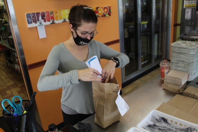 Shelby Rice, an employee at CR Juices Health Bar and Cafe in Fremont, inserts a flier reminding people to complete their 2020 Census form into a customer's bag Tuesday morning. CR Juices and several businesses took part in the 2020 Fremont City Civic Day of Action.