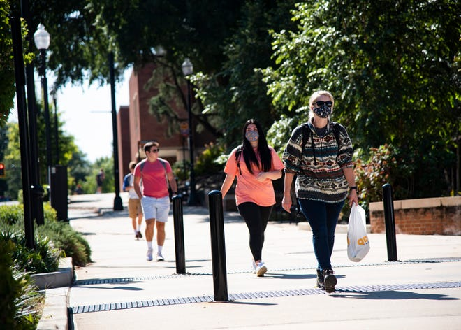 Masked students walk down Volunteer Boulevard at the University of Tennessee in Knoxville, Tenn., on Monday, Sept. 21, 2020.