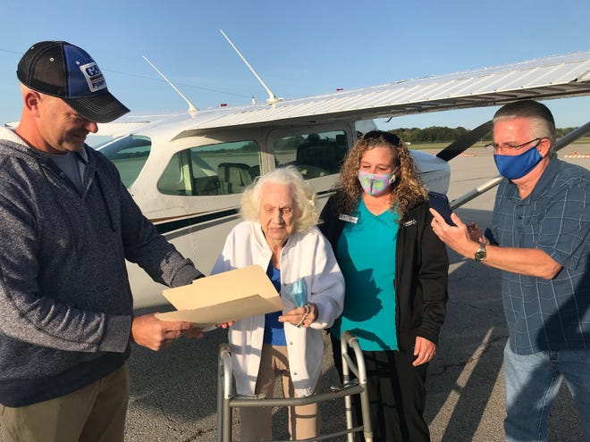 Pilot Darren Hamilton, left, gives Betty Wheeler a certificate for her first flight Monday. With them is Marti Hardin, hospice aide, and chaplain Dan Crouse. Betty completed a bucket list wish with the flight.