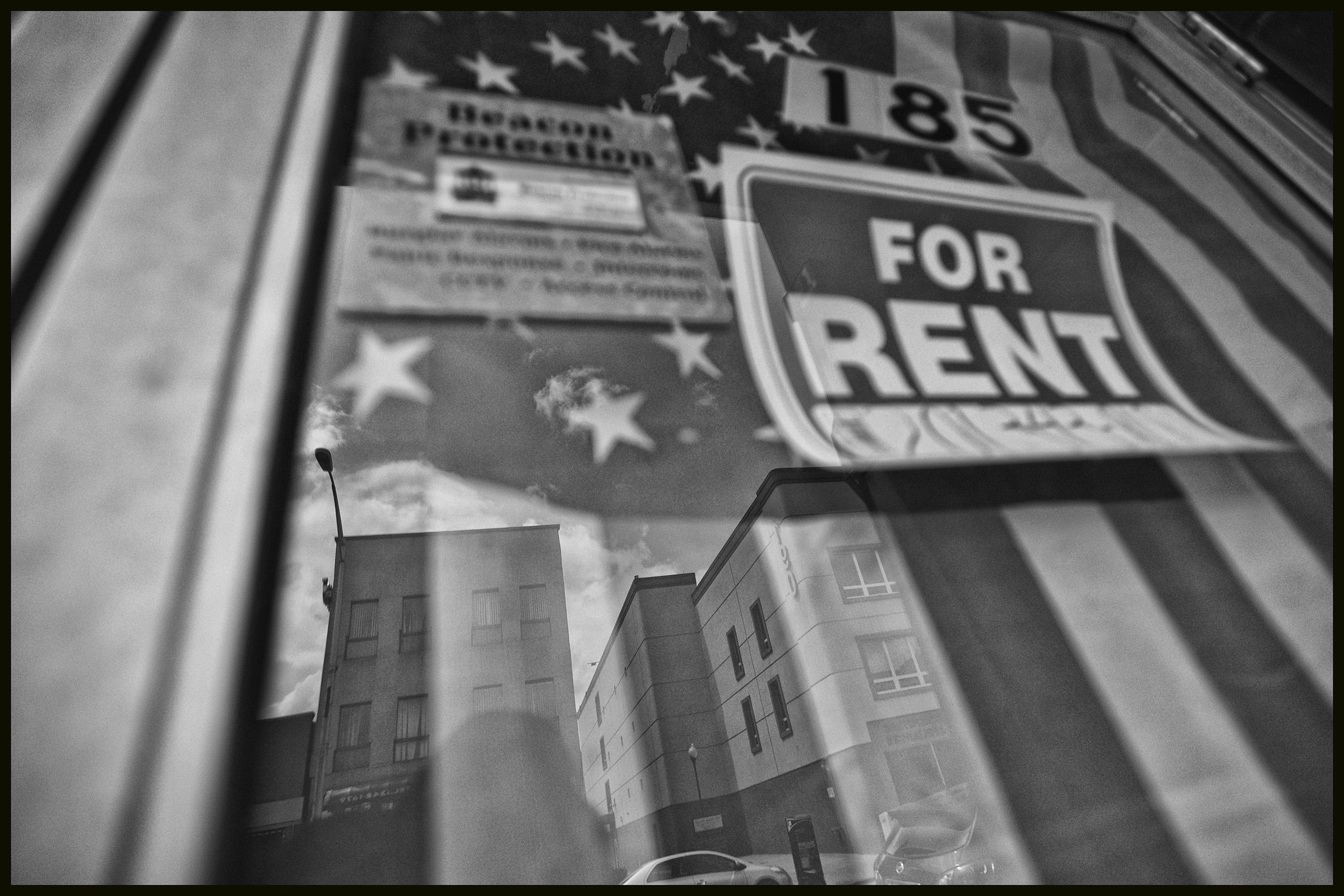 A for rent sign hangs in front of an American flag on a storefront door on Main Street in Hackensack.