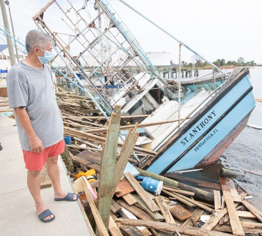 Linh Tran looks at the wreckage of his fishing boat, the St. Anthony, on Sept. 22 after Hurricane Sally sank the boat in the small harbor behind Joe Patti's Seafood in Pensacola.