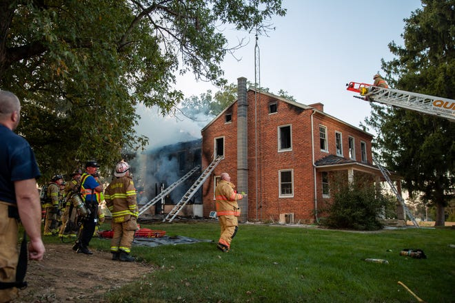 Firefighters work at the scene of a working house fire with entrapment on the 600 block of Bender Road, Monday, Sept. 21, 2020, in Mount Pleasant Township. A young girl was rescued from the second floor of the house by a volunteer firefighter that came upon the scene.
