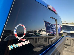 A Q sticker placed on a car parked outside the Veterans Memorial Coliseum ahead of a rally for President Donald Trump on Feb. 19, 2020.