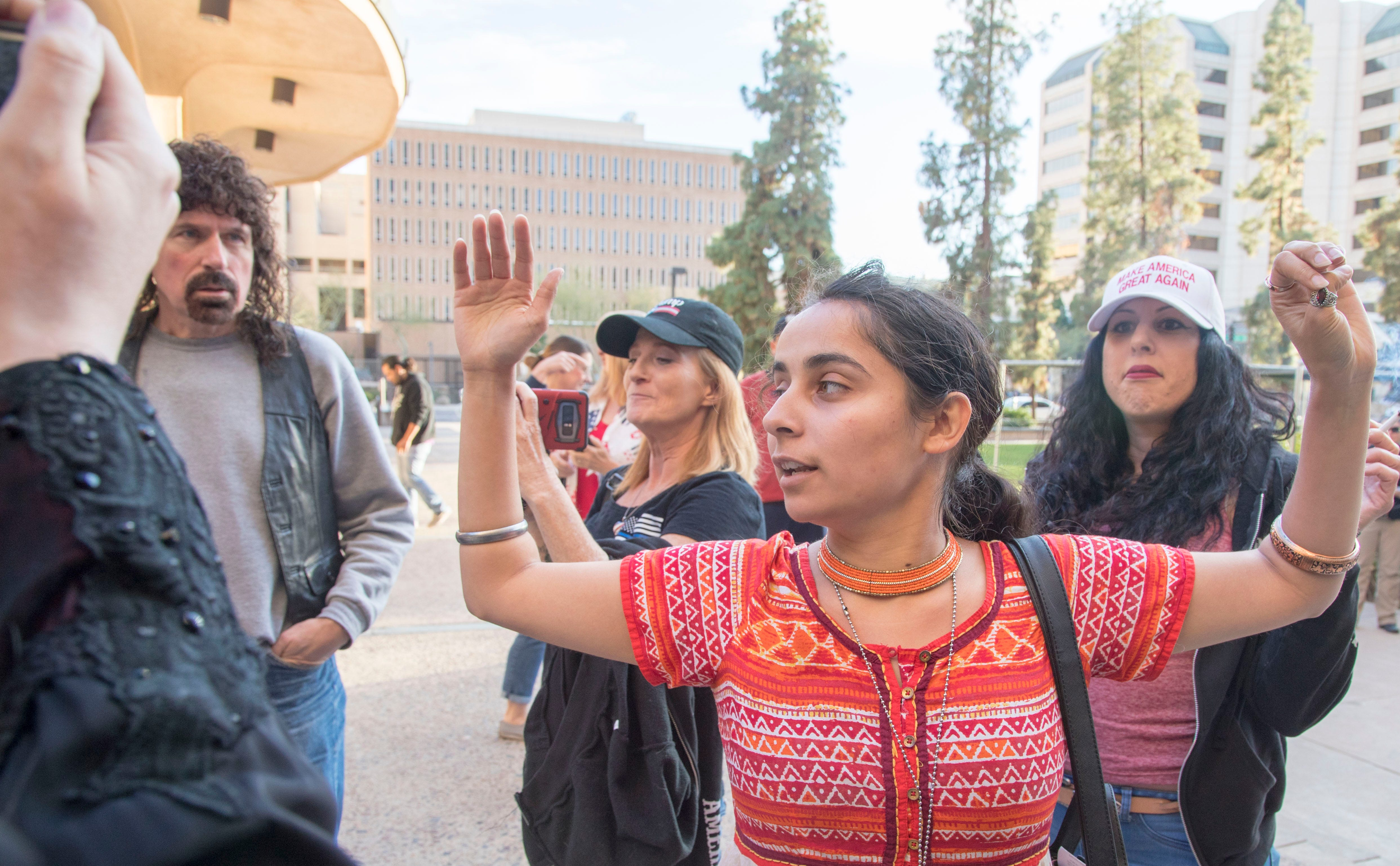 Trump supporters, including Jennifer Harrison (right), and members of Puente Arizona argue outside the Phoenix City Hall on Feb. 21, 2018.