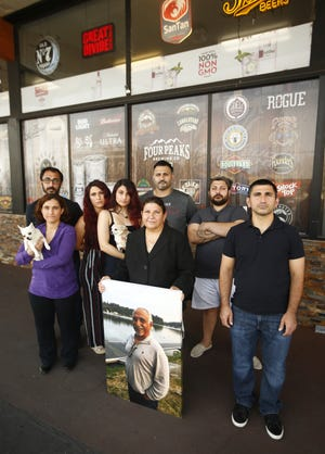 The Hanna family holds a picture of father and husband Salim Hanna at Gilbert Convenient Mart in Gilbert on Sept. 17, 2020.