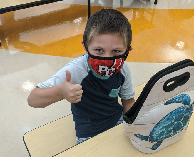 Gannon Schenko, a student at Bataan Memorial Primary School in Port Clinton, gives a thumbs up at lunch time while wearing his mask when not eating.