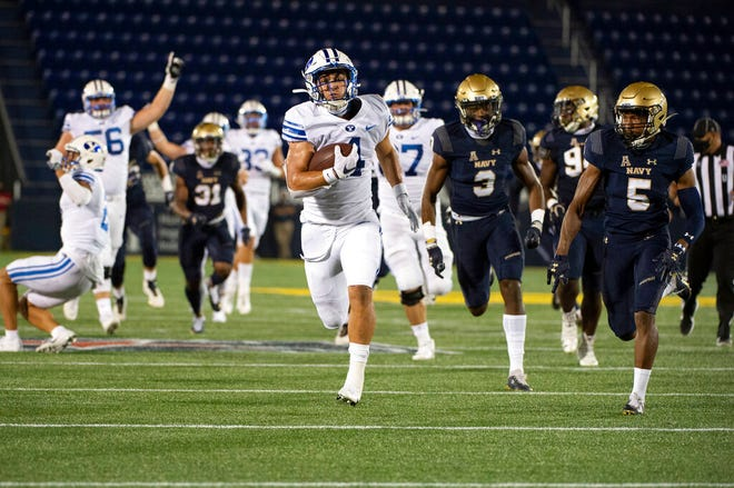FILE - Pada file foto Senin 7 September 2020 ini, BYU berlari kembali Lopini Katoa berlari untuk touchdown ketika cornerback Angkatan Laut Michael McMorris (5) dan bek defensif Cameron Kinley (3) mengejar selama paruh pertama pertandingan sepak bola perguruan tinggi NCAA di Annapolis, Md. (Foto AP / Tommy Gilligan, File)