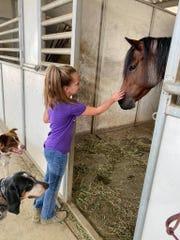 Jayme Fleeman's granddaughter, Faith, pets one of her family's horses.