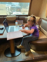 Jayme Fleeman's granddaughter, Faith, does school work on the family's RV.