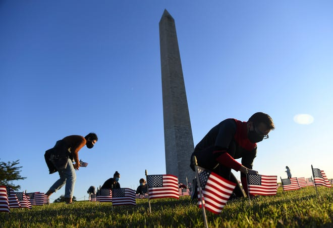 COVID Memorial Project volunteers place American flags near the Washington Monument to memorialize the 200,000 deaths due to COVID-19 Milestone on the National Mall on Sept. 21, 2020.