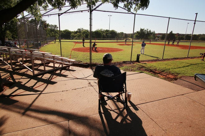 A fan follows social distancing rules to watch a youth baseball game at the A.C. Caplinger Sports Complex in Hafer Park in Edmond, Okla. on May 18, 2020.