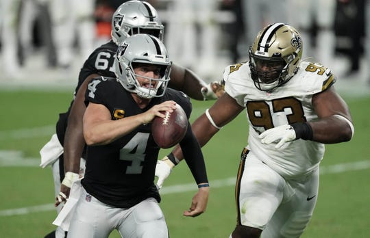 Las Vegas Raiders quarterback Derek Carr (4) runs away from New Orleans Saints defensive tackle David Onyemata (93) during the second quarter of a NFL game at Allegiant Stadium.