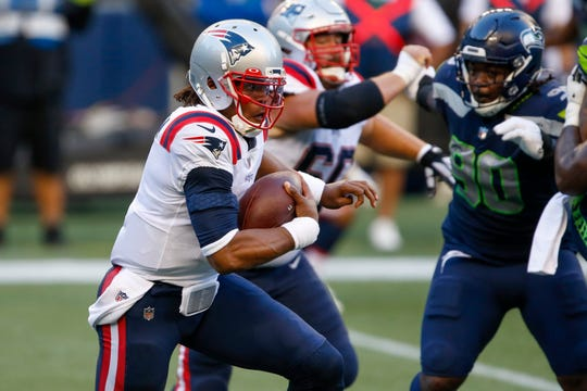 New England Patriots quarterback Cam Newton (1) rushes against the Seattle Seahawks during the second quarter at CenturyLink Field.