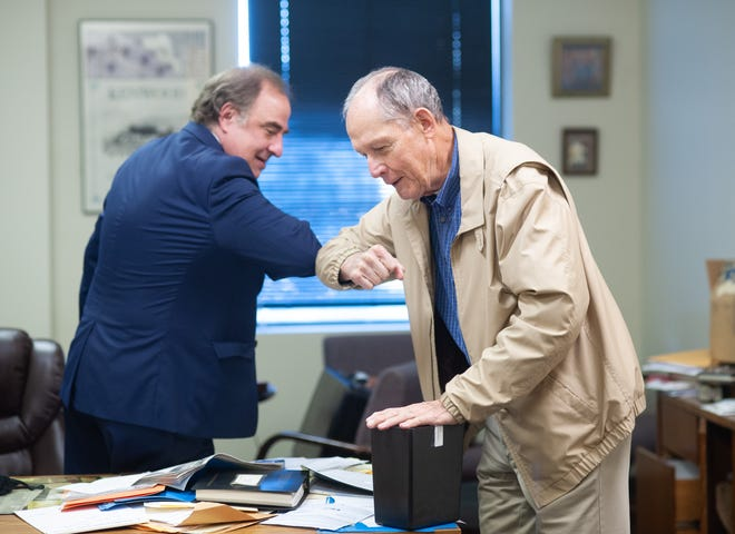 Bill Trainer (right) of Washington Crossing holds the remains of his long lost relative, Mary Reid, as he elbow bumps lawyer Ron Elgart on Sept. 23 at Law Office of Ron Elgart in Fairless Hills. (WILLIAM THOMAS CAIN/PHOTOJOURNALIST)