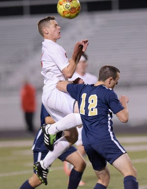 Freedom's Cal Hickenboth (4)  and Hopewell's Chris Conrad battle for the ball during Tuesday night's game at Hopewell.