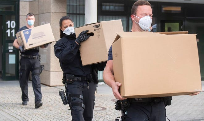 During a raid, federal police officers carry boxes of confiscated documents in front of an office building in Garbsen, Germany, Wednesday, Sept. 23, 2020. Since the early morning hours, the federal police have been conducting searches in five federal states in connection with the illegal smuggling of workers for the meat industry. About 800 officers are mainly on duty in Saxony-Anhalt and Lower Saxony, a spokesperson for the Central German Federal Police said. More than 40 residential and business premises are being searched, according to the federal police. (Julian Stratenschulte/dpa via AP)