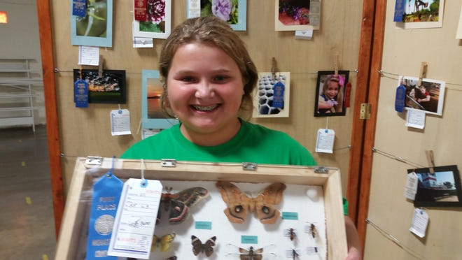 Leigha Case holds her 4-H exhibit