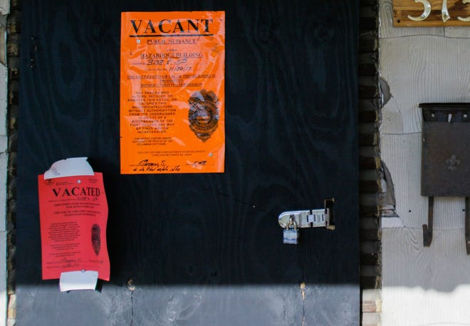 Notices prohibiting occupancy are affixed to the padlocked, boarded up front door of a Columbus house whose residents were evicted in 2017.