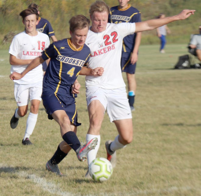 Thor Harbott battles a Detroit Lakes midfielder for possession in Crookston's 6-0 loss to the Lakers on Tuesday.