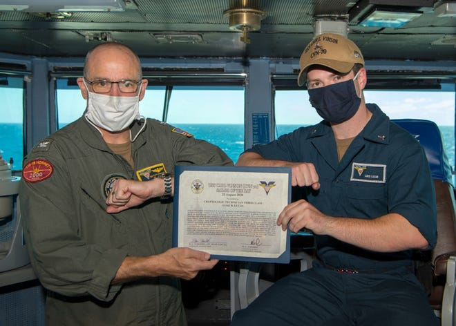 Cryptologic Technician (Technical) 3rd Class Luke B. Lucas receives a certificate from Capt.Matthew C. Paradise, commanding officer of USS Carl Vinson, after winning Sailor of the Day during a ceremony on the ship's bridge.