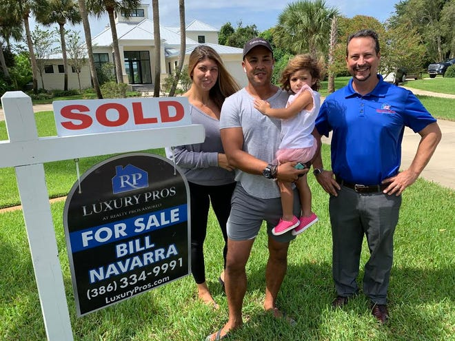 Bill Navarra, right, broker/owner of Realty Pros Assured, stands in front of a riverfront home in Ormond Beach that he recently sold to buyers Mustapha El Khorchi, pictured holding his daughter Eva, and Khorchi's wife Carlotta on Tuesday, Sept. 22, 2020. It was one of four homes Navarra sold for more than $1 million in August as home sales and prices continue to rise in both Volusia and Flagler counties.