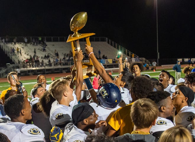 William Chrisman players hoist the Wagon Wheel Trophy after a win at Truman last year. This year's winner of the classic rivalry game will lift the trophy at Staley High School so the schools can have more fans and cheer and dance squads attend.