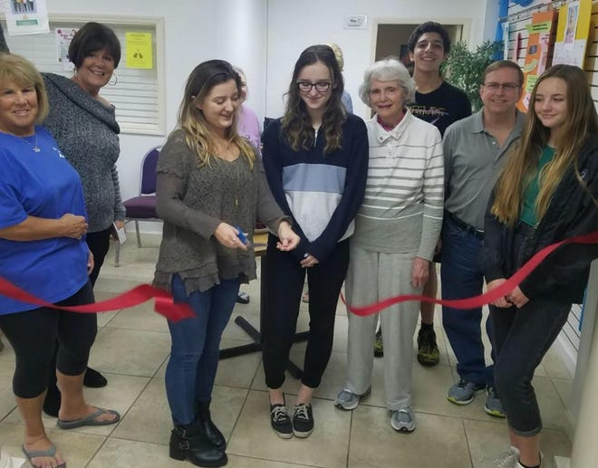 Savannah Beeler cuts the ribbon for her Golden Age Tech during a meet-and-greet with some of the Fletcher Interact Club members and Neptune Beach Senior Activity Center & Foundation attendees. The senior citizen technology-assistance program was her Gold Award project for the Girl Scouts of Gateway Council.