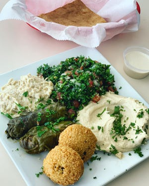The vegetarian platter touts crispy falafel, hummus, grape leaves — some of the best I've had locally — plus tabouli, baba ganoush and warm pita bread.