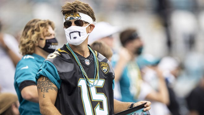 A  Jaguars fan watches the team's 27-20 victory over the Colts on Sept. 13. Masks are mandatory for all fans inside TIAA Bank Field.