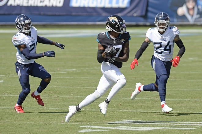 Jaguars wide receiver D.J. Chark makes a catch as he is defended by Tennessee Titans cornerback Malcolm Butler and safety Kenny Vaccaro.