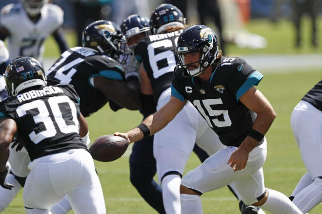 Jaguars quarterback Gardner Minshew (15) hands off to running back James Robinson (30) during the first half. Both Minshew and Robinson achieved statistical milestones Sunday. Wade Payne/AP Photo