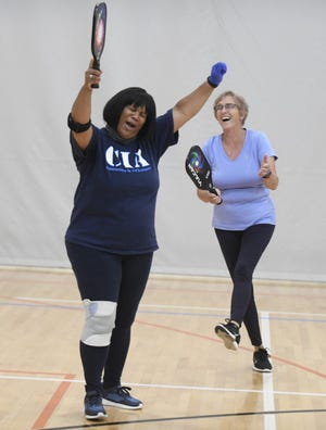 Karen Rudolph (left) and her pickleball partner, Kathy Harper, celebrate scoring a point Wednesday afternoon at the Massillon Recreation Center. The Recreation Department voted 4-0 on Wednesday, approving a November membership drive that aims to cut rates for new 1-year and 3-month memberships by 50%. The final decision goes to City Council.