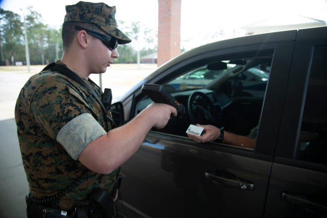 A U.S. Marine Corps gate sentry scans a military ID at a gate on Marine Corps Base Camp Lejeune in March.