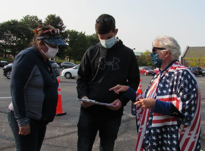 Marti Franks, right, helps Tyler Hoffman, 18, a recent high school graduate, with the voter registration process. Tyler came with his mother Karen. This will be Tyler's first election where he is eligible to vote.  The Hoffmans live in Solon.