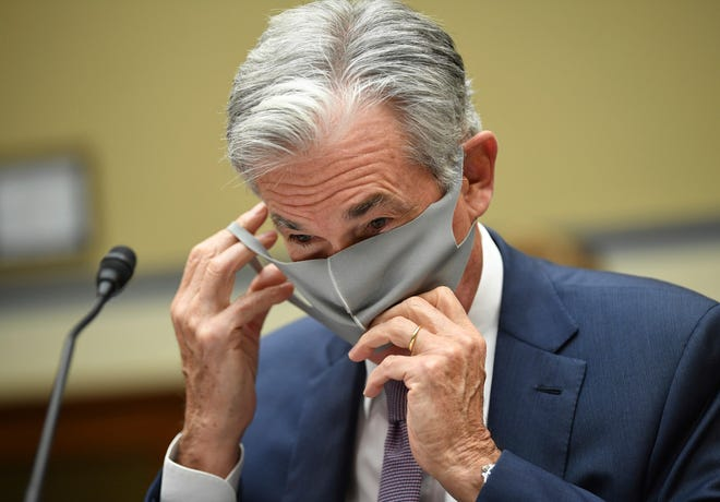 Federal Reserve Chair Jerome Powell takes off his face mask to testify during a House Select Subcommittee on the Coronavirus Crisis hearing on Capitol Hill in Washington on Wednesday.