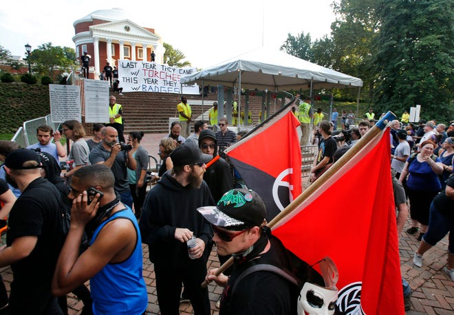 "FILE - In this Saturday, Aug. 11, 2018 file photo, A group of anti-fascist and Black Lives Matter demonstrators march in front of the Rotunda on the campus of the University of Virginia in August 2018 in anticipation of the anniversary of the previous year's Unite the Right rally in Charlottesville, Va. Rutgers University historian Mark Bray, author of the book ""Antifa: The Anti-Fascist Handbook,"" said there are well organized, tightly knit antifa groups that have operated for years. ""But that's different from saying that the politics of antifa is just one single, monolithic organization, which is obviously false,"" said Bray, whose book traces the history and evolution of the movement."