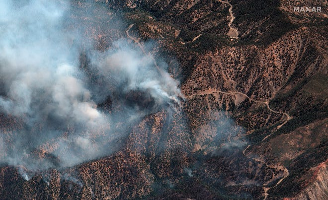 This natural color photo provided by Maxar Technologies shows fire spots from the Bobcat Fire amid an area of the Angeles Crest Highway winding through the San Gabriel Mountains, in Los Angeles County, California, on Monday.