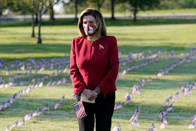 House Speaker Nancy Pelosi pauses Tuesday and looks at small flags placed on the grounds of the National Mall by activists from the COVID Memorial Project to mark the deaths of 200,000 lives lost in the U.S. to COVID-19.